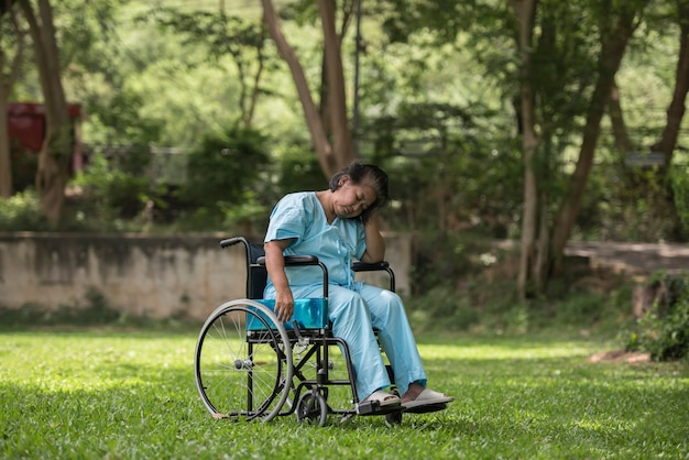 Lonely elderly woman sitting sad feeling on wheelchair at garden in hospital