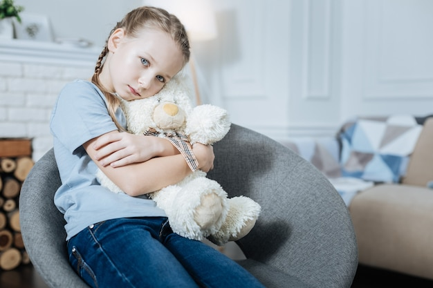 Lonely fair-haired blue-eyed little girl hugging and holding her teddy bear while sitting in the armchair