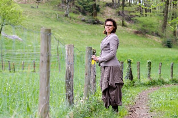 나무 울타리와 함께 공원에서 산책하는 외로운 여성