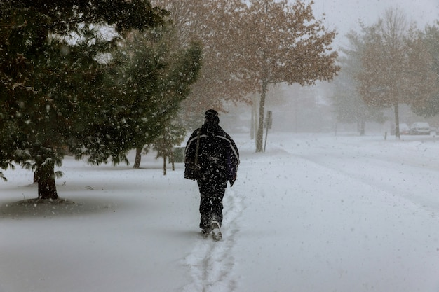 Lonely figure of human on a snowy road during the snowfalls in winter