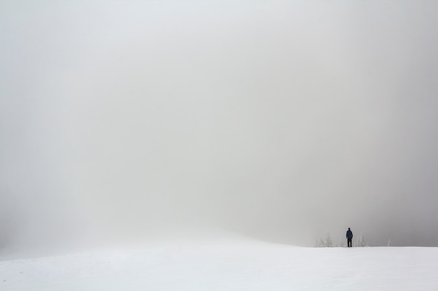 Lonely figure of a man standing outdoors in winter