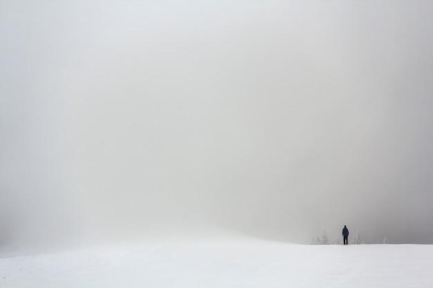 冬に屋外で立っている人の孤独な図