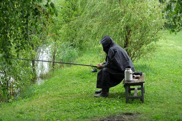 雨の夏の天候で湖の孤独な漁師。レインコートで釣りをしている漁師