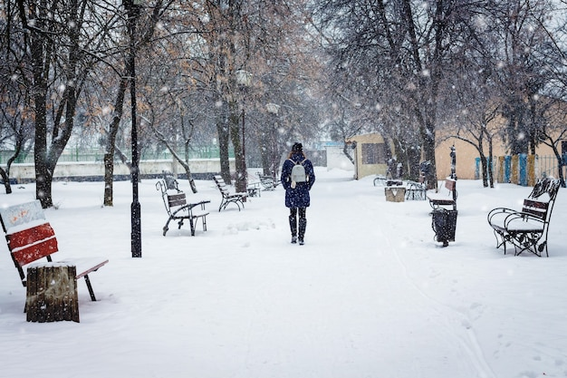 Lonely girl in a city park during a blizzard