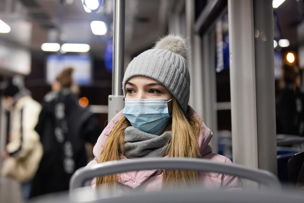 Lonely girl in a face mask rides a tram at night in pandemic time