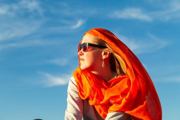 Одинокая девушка в пустыне сахара на закате. эрг шебби, мерзуга, марокко.