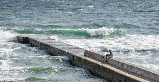 Lonely girl on the pier around the stormy sea