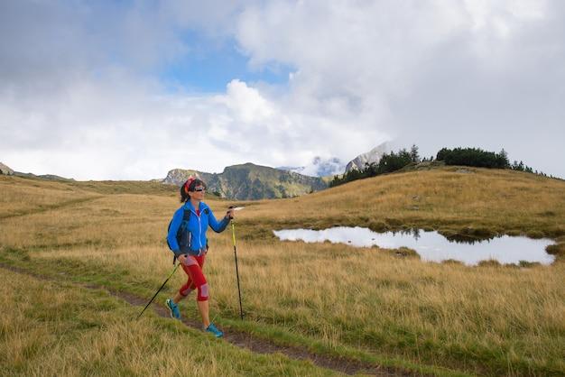 Одинокая девушка, практикующая нордическую ходьбу