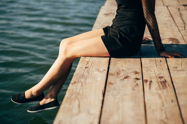 Lonely girl sitting on the pier in summer