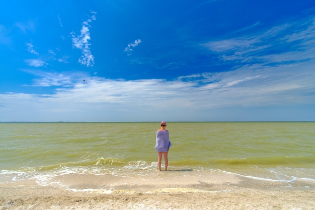 A lonely girl stands in the water on the surf line, wrapped in a towel. summer sunny day at the seaside resort.
