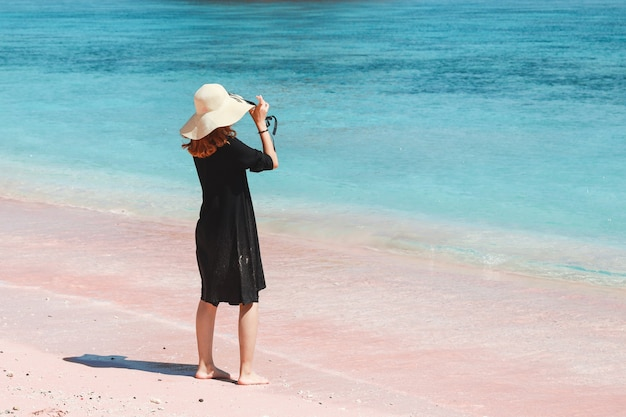 Lonely girl in summer hat standing and enjoying sea view on pink sand beach