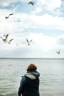 A lonely girl in a tank top and a pink sweater with a hood feeds seagulls by the sea.