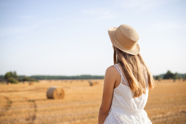 Lonely girl in a white dress, straw hat sitting on a bale in the agricultural field after harvesting