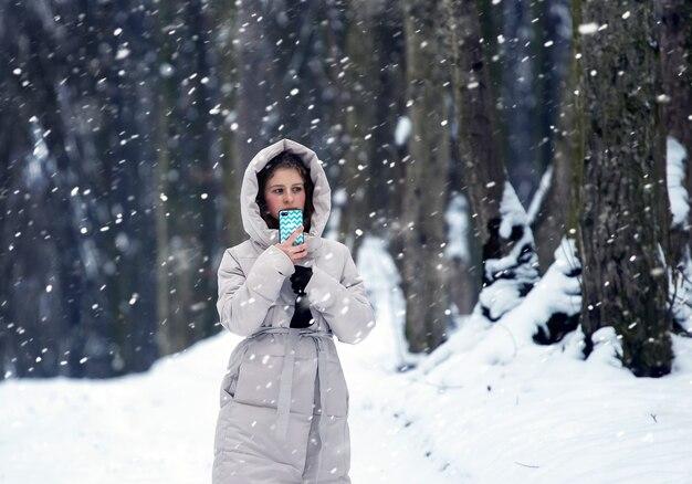 吹雪の間に森の中で彼女の手に携帯電話を持っている孤独な少女。冬の森を散歩