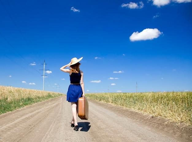 田舎道でスーツケースを持った孤独な少女。