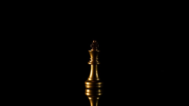 Lonely golden king chess standing in the dark.
