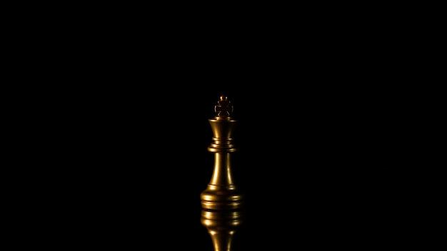 Одинокий золотой король шахмат, стоящий в темноте.