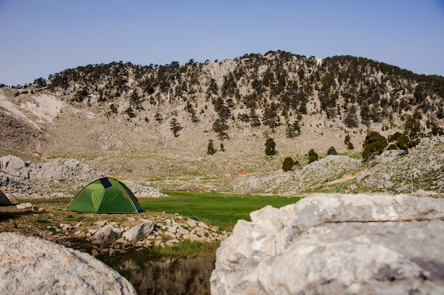 Lonely green tent in a mountain valley