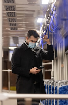 Lonely guy in a face mask rides a tram at night in pandemic time