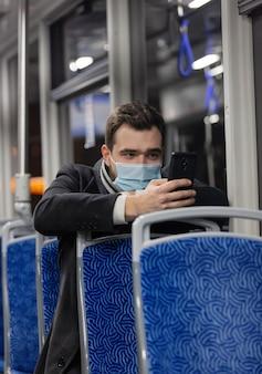 얼굴 마스크를 쓴 외로운 남자가 유행성시기에 밤에 트램을 타고