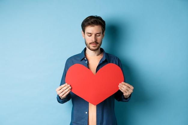 파란색 배경 위에 서 슬픈 얼굴로 발렌타인 붉은 마음에 슬픈 찾고 외로운 남자.