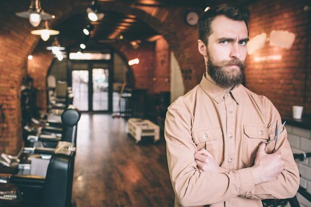 Одинокий парикмахер в комнате. он держит в руке ножницы и ждет покупателя. парень выглядит очень серьезно.