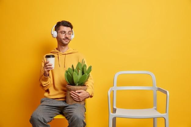 孤独なハンサムな男が一人で自由時間を過ごす、鉢植えのサボテンの持ち帰り用のコーヒーを持ち、空の椅子を見て、ヘッドフォンで音楽を聴く