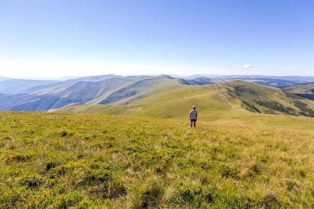 山に立っている孤独なハイカー。観光客の男は山の景色を楽しむ