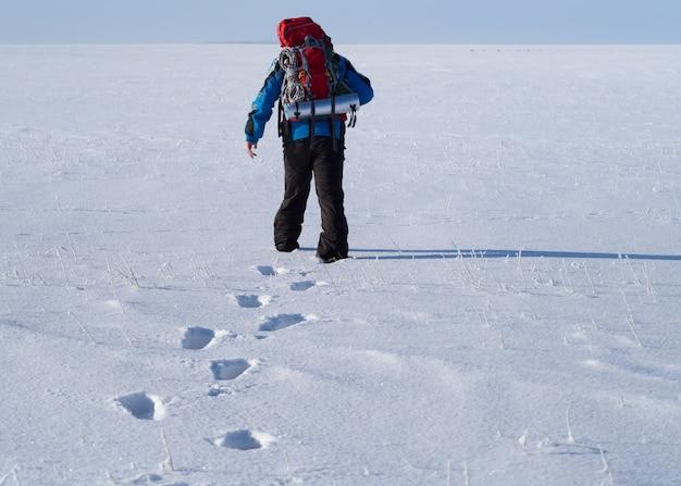 Одинокая человеческая прогулка по снежной пустыне. следы на заснеженном поле. вид сзади.