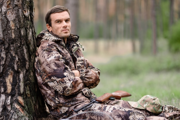 Lonely hunter in camo has rest sitting under tree