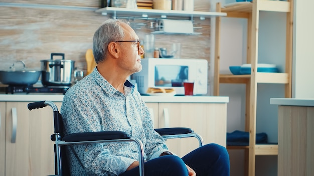 Lonely invalid man sitting in wheelchair looking through kitchen window. elderly handicapped pensioner after injury and rehab, paralysis and disability for depressed invalid full of sorrow, worry and