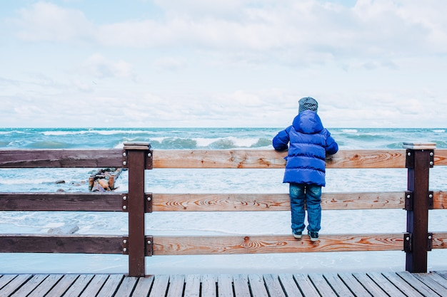 A lonely kid in blue jacket and jeans at the beach looking at the stormy sea staying on a fence. winter or late autumn season