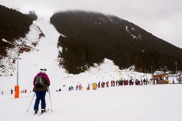줄을 서서 눈 산에서 스키를 기다리는 동안 큰 그룹 사람들 앞에 서있는 외로운 아이 스키어.