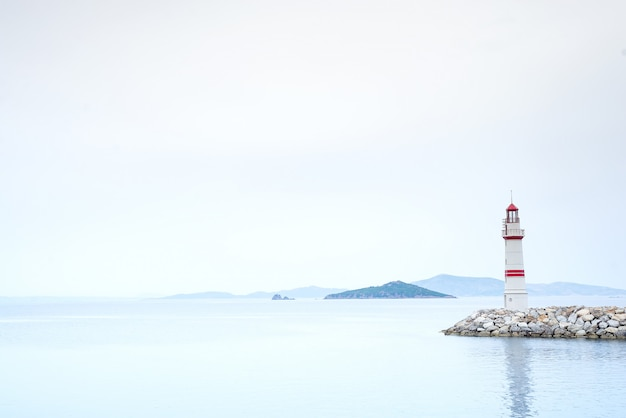 Одинокий маяк на каменной дороге посреди моря с видом на горы и туман