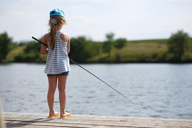 Одинокий маленький ребенок, ловящий рыбу с деревянной пристани на озере.