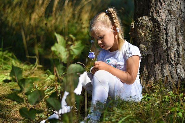 Lonely little girl in a white dress and a flower in her hand sits near a tree in the afternoon