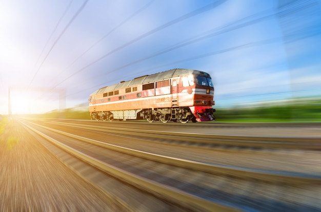 Lonely locomotive rushes by train at sunset.