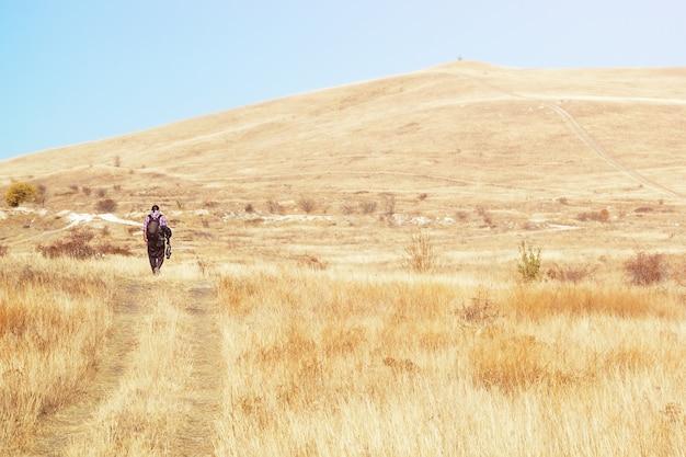 외로운 남성 사진가가 수평선, 휴가, 여행의 대초원을 걷고 있다