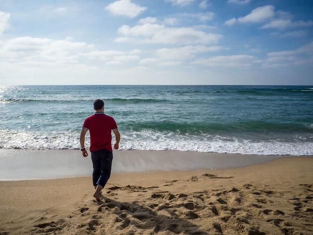 Maschio solo che cammina sulla spiaggia sotto il bel cielo nuvoloso