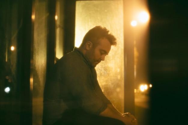 夜の街のバス停で孤独な男