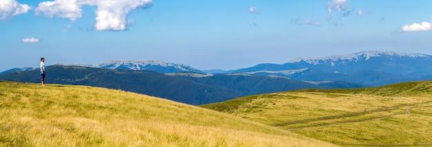 Одинокий турист, стоящий на широком холме с видом на горы