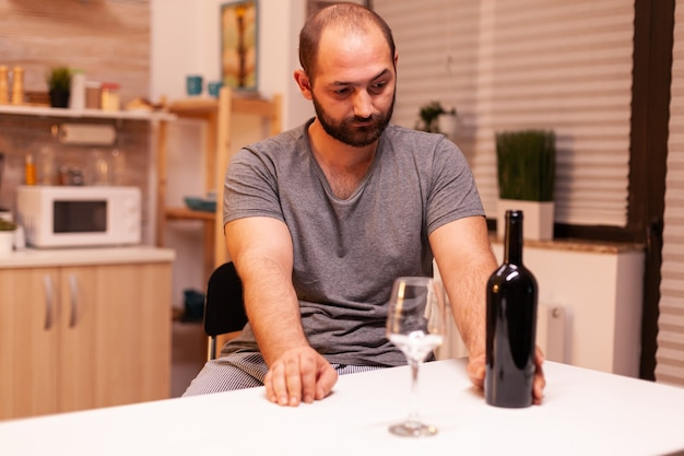 Lonely man holding bottle of red wine because of depression. unhappy person disease and anxiety feeling exhausted with dizziness symptoms having alcoholism problems.