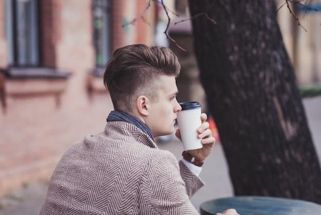 孤独な男が通りのカフェに座っている間行くコーヒーを保持しています。