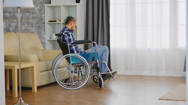 居間で歩行障害のある車椅子の孤独な男。