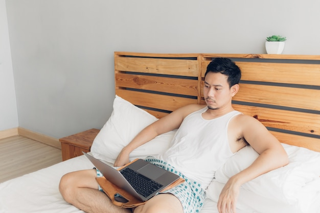 Lonely man is working with his laptop on his cozy bed.