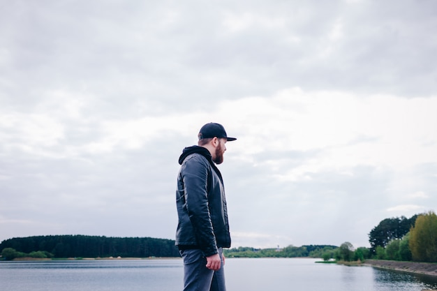 A lonely man in a leather jacket near the river