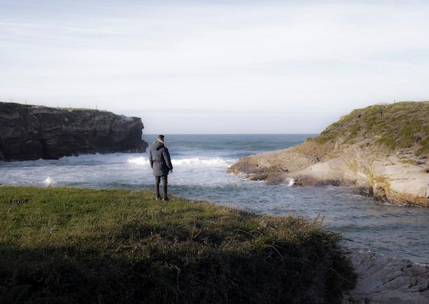 海の近くの崖の上の孤独な男