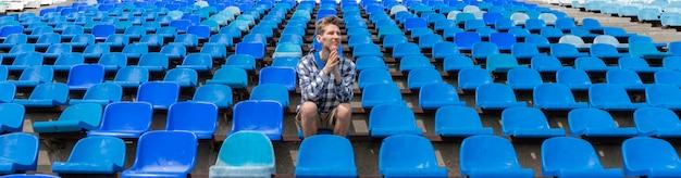 Одинокий мужчина на пустом месте стадиона болеет за команду, концепции одного человека в армии