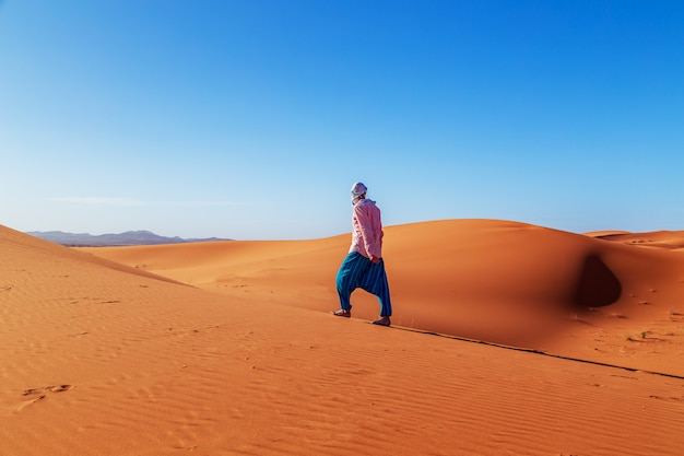 Lonely man in the sahara desert