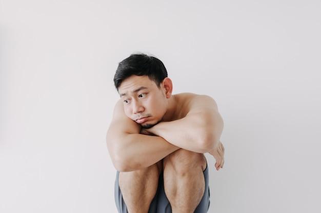 孤独な男が座って、白い背景で隔離の膝の上で休む